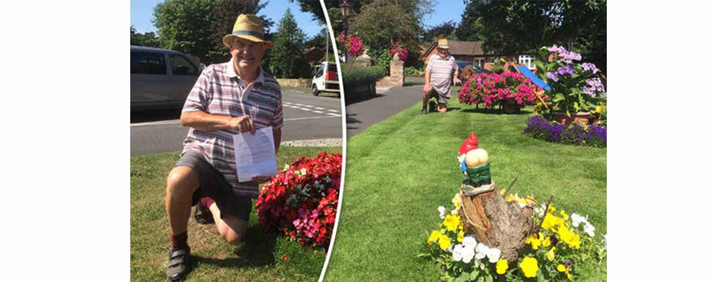 Happy Guy With Show Off His Garden Gnome Certificat On Grass Beside Flowers