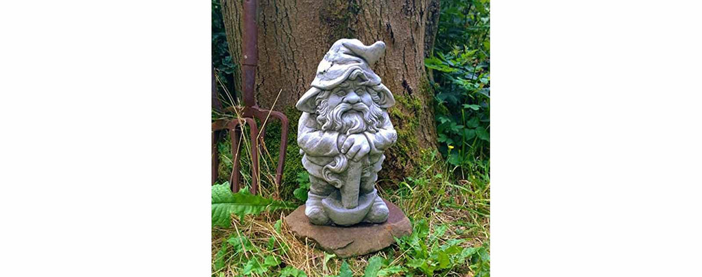 Old Garden Gnome Beside a Giant Tree in the Forest