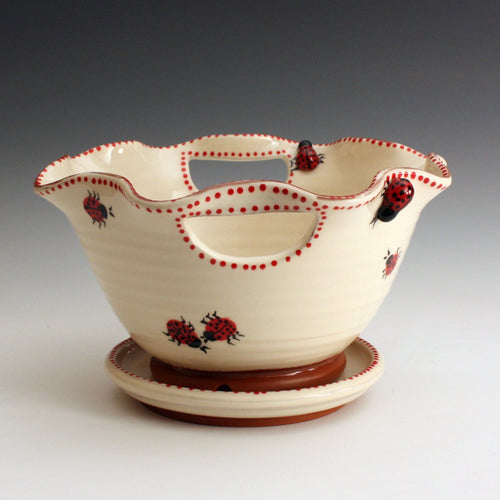 Berry bowl with saucer.  Made of red eartheware clay it decorated white with red dots and red lady bugs both two and three dimensional.