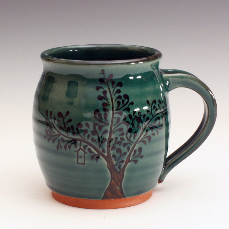 Red earthenware mug with green glaze.  The trunk is carved into the clay and black decoration for the leaves.  Some contain bird houses carved in.  The roots are carved into the base of the mug.