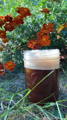 a mason jar with a frothy coffee drink sits in a bed of greenery with burnt orange flowers in the background