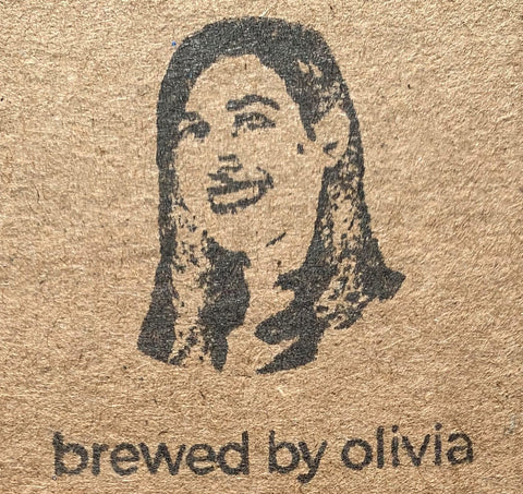 """A image of a woman's head and the words """"brewed by Olivia"""" stamped in black in on a brown cardboard background."""