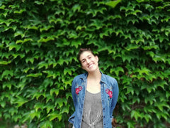 A woman, wearing a denim shirt and standing in front of a wall of leaves