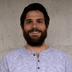 A bearded smiling man with a light background