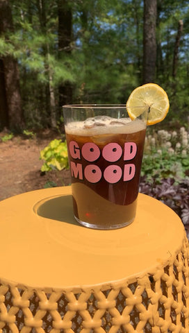 Glass of cold brew coffee on a yellow table, garnished with a slice of lemon