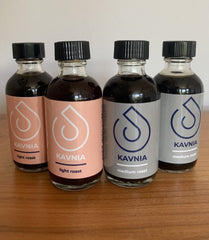 four small bottles of coffee. the left two with pink labels and the right two with grey labels