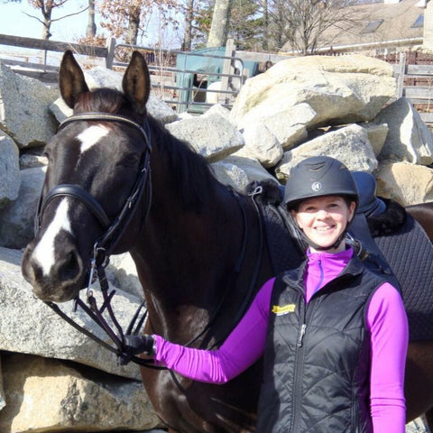 Rider standing next to her horse