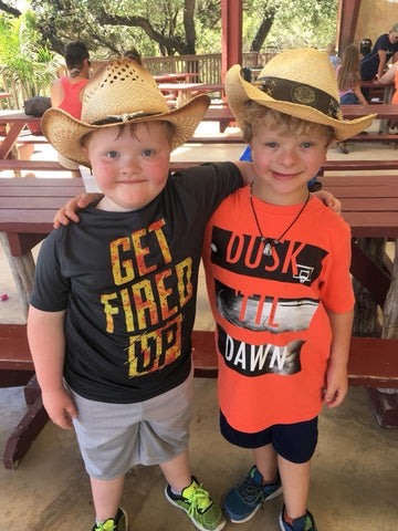 Two young boys in cowboy hats with interlinked arms