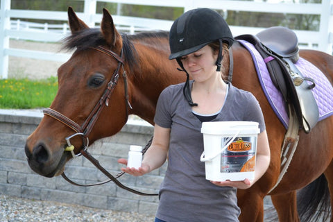 Woman and horse standing holding a bottle of pills and Bute-Less Performance Supplement