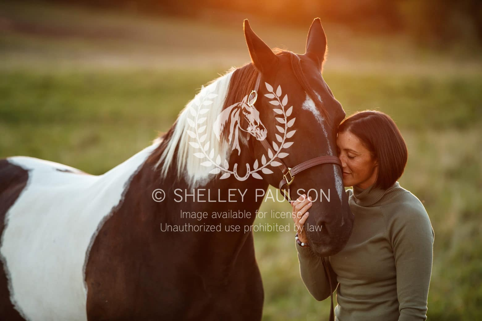 A woman nuzzles her horse