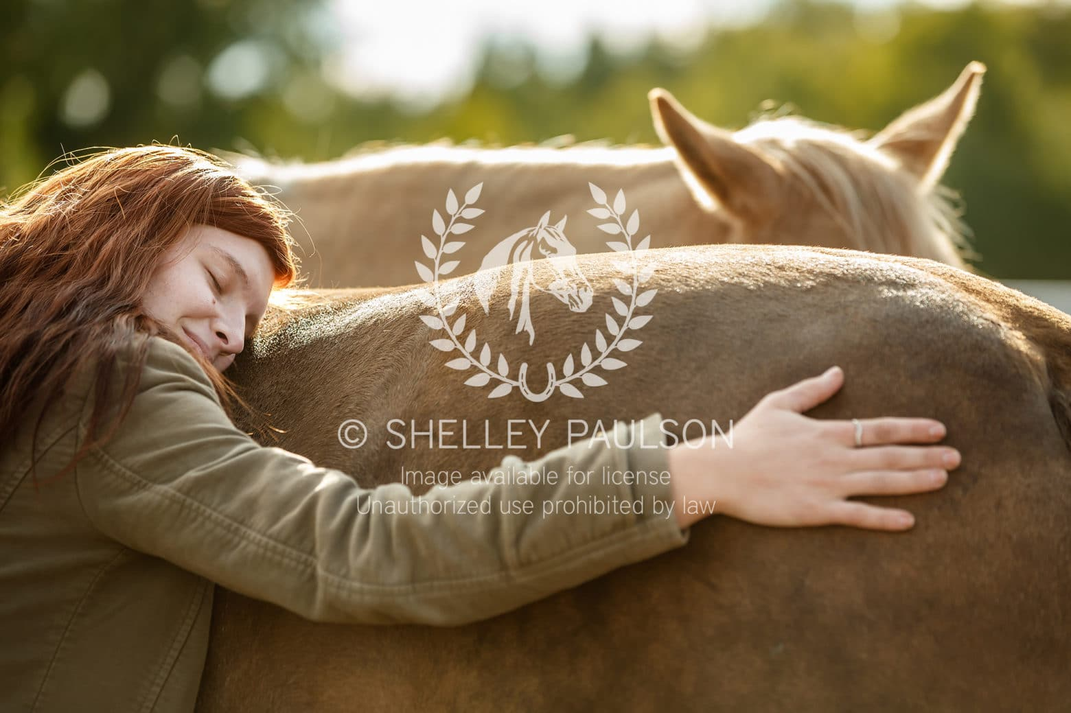 A young woman hugs her horse