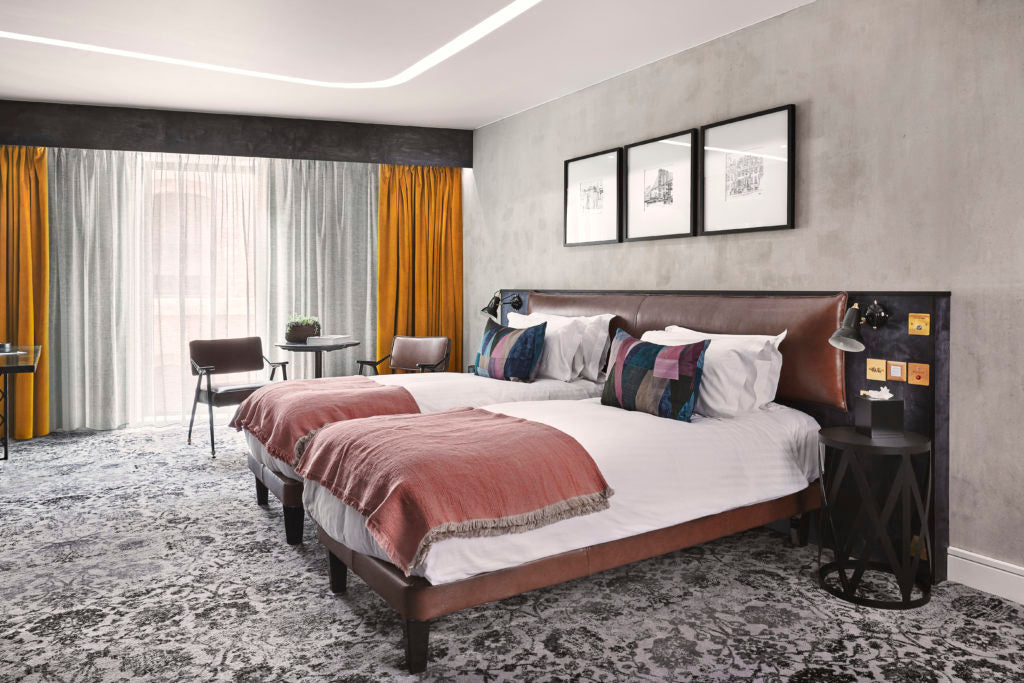 Hotel Brooklyn bedroom. A recessed lighting feature curves around the entire ceiling above a double bed. A chair and table in front of a large window are beside the bed.