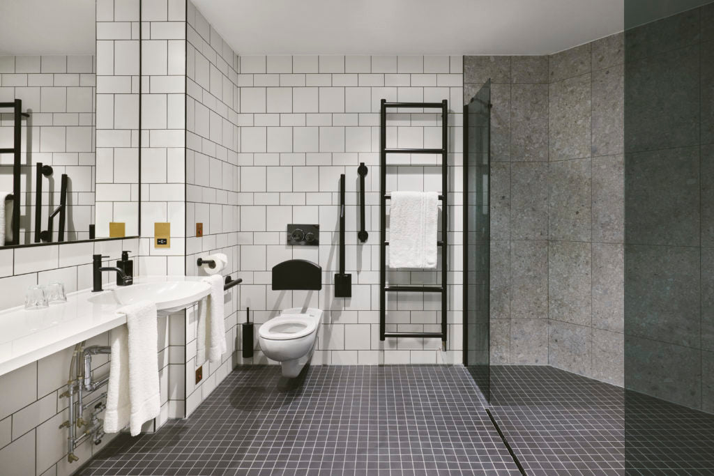 monochrome level access wetroom with subway tile and matt black brassware.