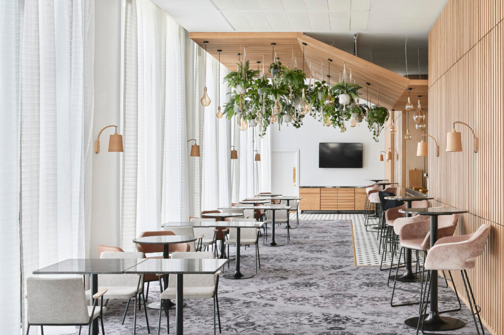 A dining area within Hotel Brooklyn with various size and shaped table and chair options and a wide walkway. Plants hang from a wooden ceiling