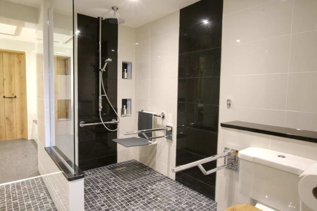 A black and white tiled shower room featuring chrome grab rails and a grey shower seat with built-in storgae niches next to the shower