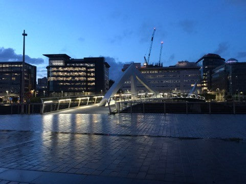 A night scene of a bridge leading to the Glasgow Barclays campus