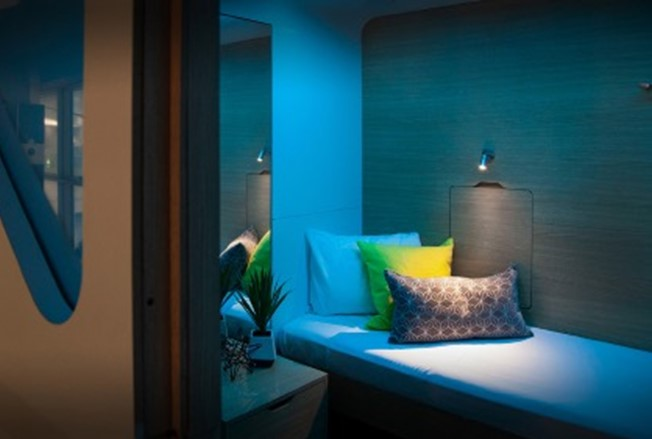 Recalibration space, small room with soft lighting and bed with cushions
