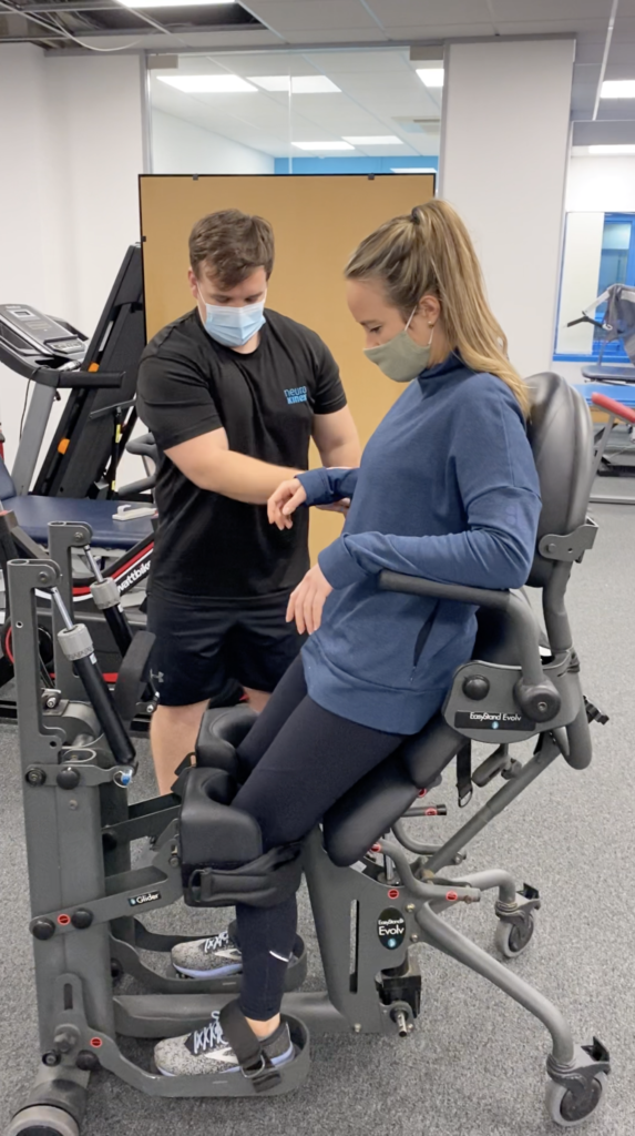 Becky being raised from seated to standing in a piece of gym equipment assisted by a trainer