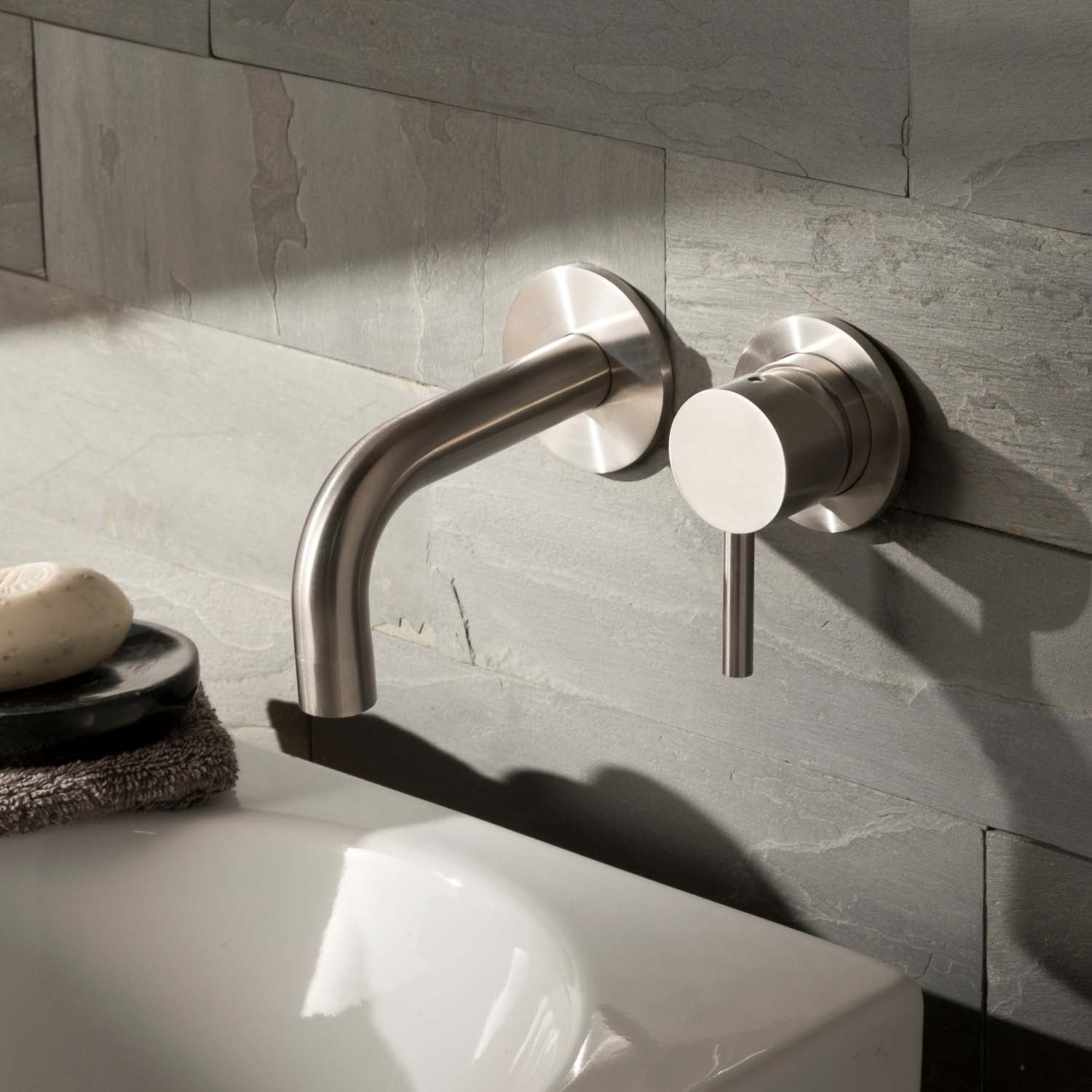 Two hole wall mounted Libero Wall Mounted Basin Tap with a 155mm spout and satin steel finish lifestyle image
