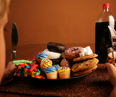 A child sits in front of a plate filled with sugary foods and a cup of soda.