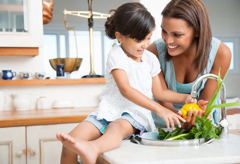 A little girl and her mom wash vegetables in the sink together.