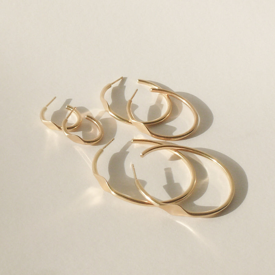 gold signet hoop earrings on white with shadow