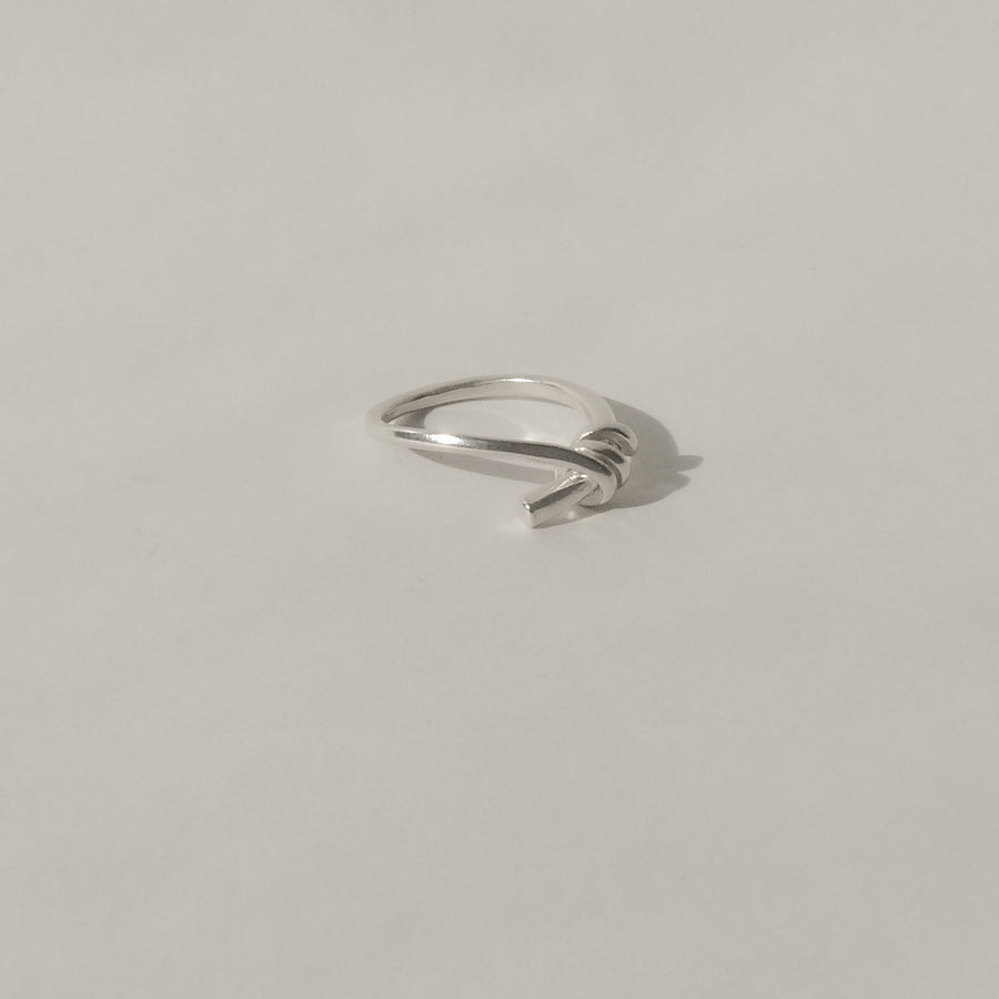 silver knot ring on white with shadow