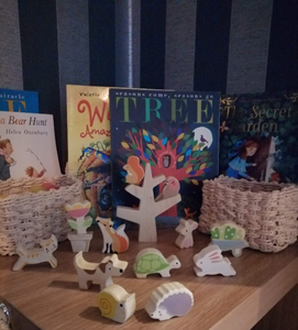 A seasonal interest table including wooden animals, loose parts and books.