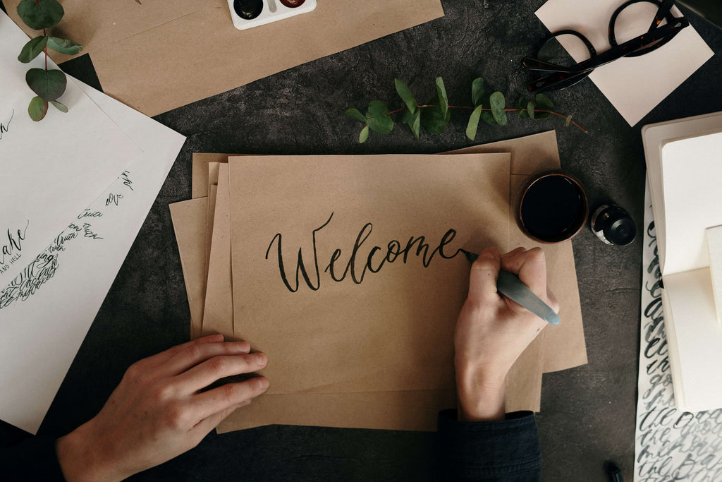 A person writing 'welcome' in a relaxed calligraphy style on brown paper. Text on websites must be clear and readable to successfully sell a product or service.