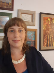 A headshot photograph of a mature woman with medium-length light brown hair cut away from her face with short bangs, in a dark blazer and a white necklace.  Behind her are framed landscape prints on a white wall.