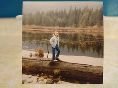 A young girl around 10 poses standing on a log near a lake with marsh and trees on the opposite shore behind her.