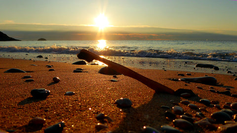Picture of a wooden toothbrush on a sandy beach.