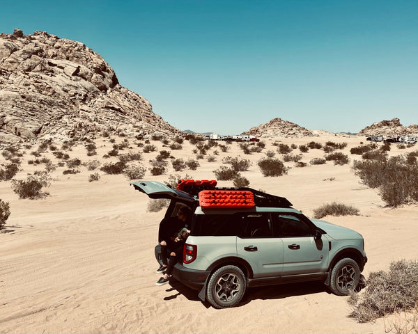 A mom and her daughter sitting on the tailgate of their Bronco Sport in the desert.