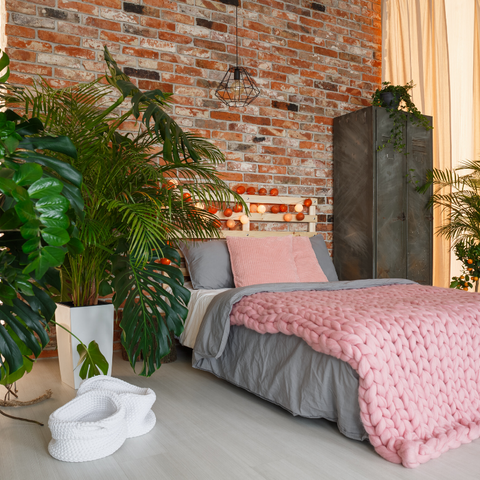 Modern bedroom with redbrick wall and large plants