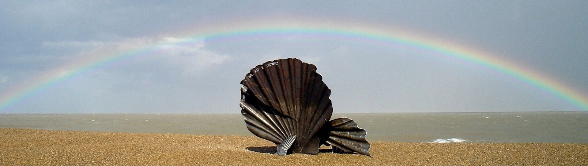 the scallop with low arching rainbow out to sea perfectly centered