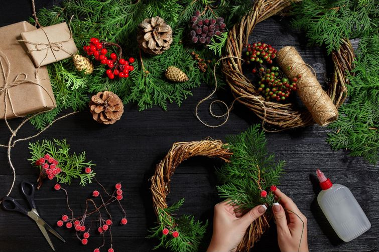 DIY Christmas wreath supplies, including holly, pine cones, and branches