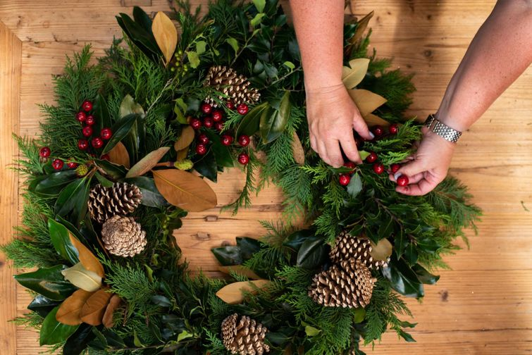 person making Christmas wreath