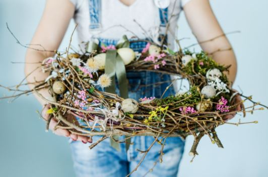 Woman in overalls holding DIY spring wreath