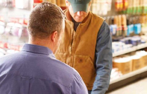 man in blue shirt helping man in beige vest at store