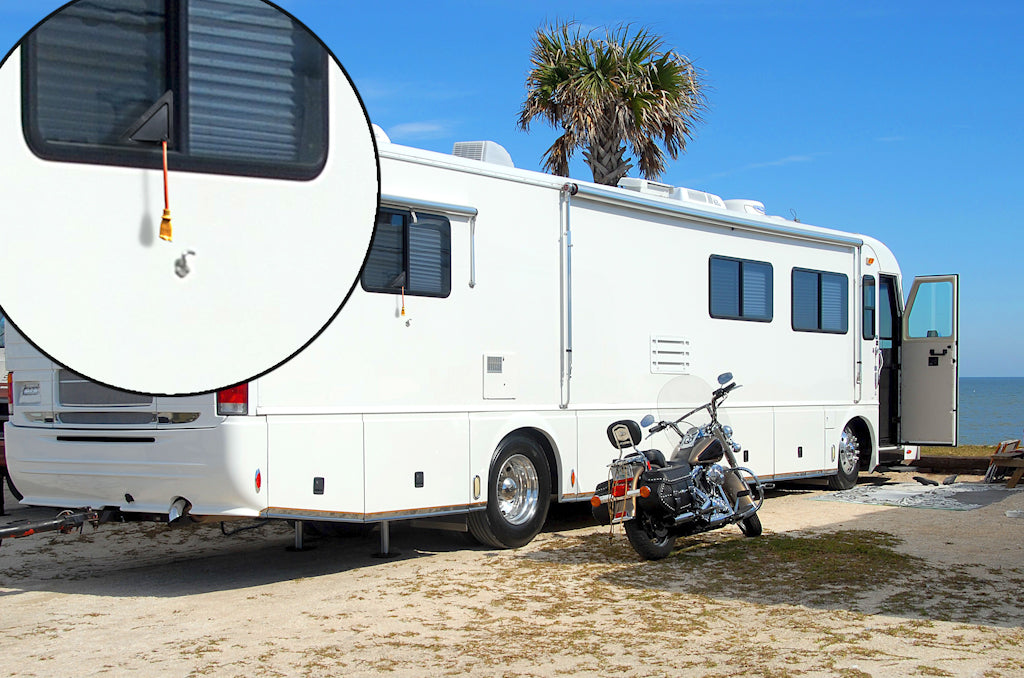 A large camper on the beach with a window screen insert for power cords - ScreenLet