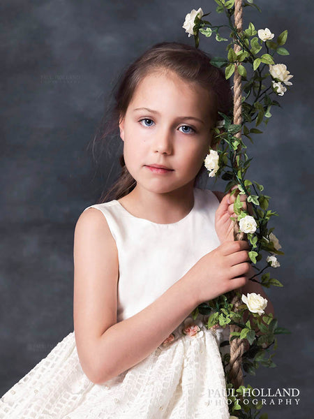 Fine Art Portrait by Paul showing a young girl holding the rope handle of a swing covered in flowers