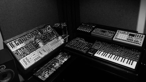 Black and white photo of a corner desk with two Eurorack systems and a selection of synths and keyboard.