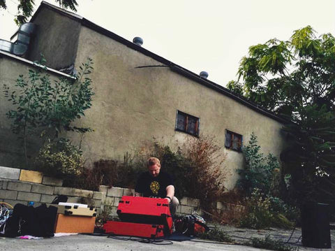 Patrick performing on a red modular system sitting on the ground in front of an old house.
