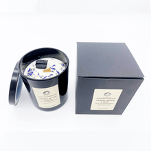 Load image into Gallery viewer, A picture of a large white candle sprinkled with flower petals and a crystal imbedded in it next to the box it comes in.