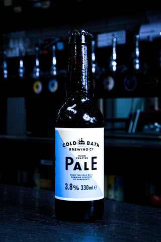 An ice cold bottle of Cold Bath Brewing Co's Pale Ale with their trademark yellow and blue sticker, sat on top of a alcohol bar counter