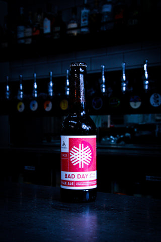 An ice cold bottle of Alechemy Bad Day At The Office Session IPA, with red stickers and a beer perfect to lighten your day after a tough working day. Served on a bar top in an ice cold bottle, in front of beer pumps and beer taps.