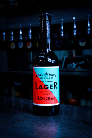 An ice cold bottle of Cold Bath Brewing Co Lager on a bar top