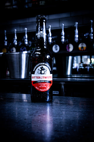 An ice cold bottle of Harviestoun Brewery Old Engine Oil sat on top of a bar