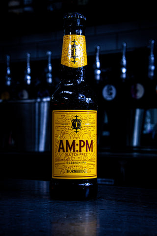 An ice cold yellow bottle of AM:PM, a Session IPA by Thornbridge Brewery. Sat on top of a bar.
