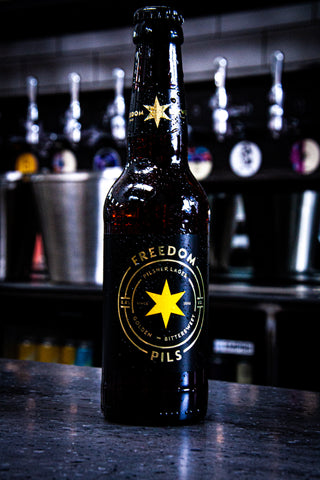 Freedom Brewery's Freedom Pilsner Lager - Golden Bittersweet, a bottle sat on top of the bar in a taproom, in front of beer kegs, beer pumps and beer taps.
